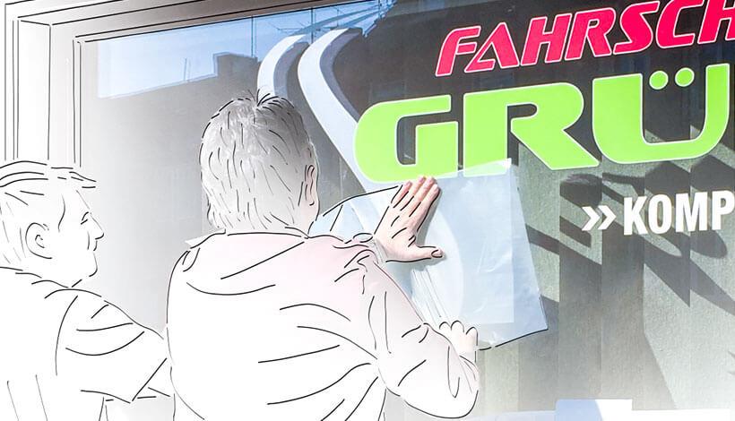 Werbetechniker beklebt das Schaufenster